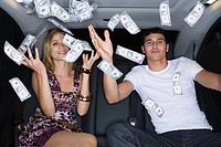 Wealthy couple celebrating in a car (thumbnail)