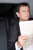 Businessman reading a newspaper in a car