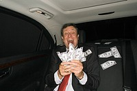 Businessman counting money in a car