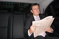 Businessman reading a newspaper in car