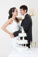 Newlyweds standing near wedding cake