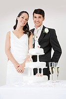 Newlyweds standing by wedding cake