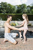 Father and daughter by the swimming pool