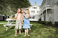 Children eating ice lollies in garden