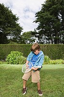 Boy playing guitar on a tennis racket