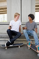 Teenage boys with cellphones and skateboards