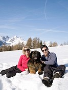 woman and man in snow with big dog