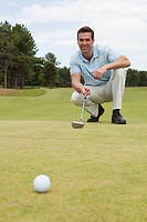 Male golfer crouching on green (thumbnail)
