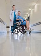 Doctor standing with patient in wheelchair