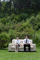 business woman and man sitting on Couch on a lawn