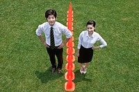 businessman and woman standing with traffic cones