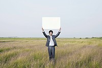 businessman holding a notice board, outside
