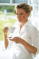 woman at home drinking a cup of coffee