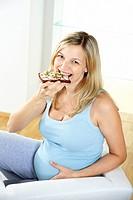 junge schwangere frau isst vollkornbrot
