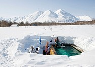 Outdoor hot natural hot spring bath in deep snow at a countryside Dacha in Kamchatka in the Russian Far East