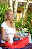 young blonde woman doing yoga on tropical garden in Thailand