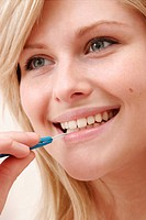 Young woman cleaning teeth with interdental