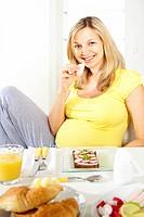 junge schwangere frau am frühstückstisch