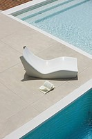 Open book lying on ground next to poolside deckchair, high angle view (thumbnail)