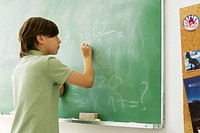 Boy writing with chalk on blackboard