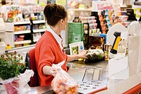 Cashier totaling grocery purchases (thumbnail)