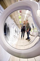 Shoppers seen through open washing machine door