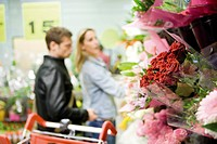 Flower bouquets at flower shop, couples browsing in background