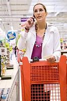 Woman using cell phone in supermarket