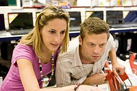 Couple together in electronics section of department store, shelf of laptops in background