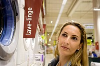 Woman looking at washing machine on display in department store