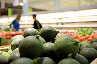 Globe zucchini display in supermarket produce section