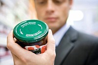 Man reading label on jar of jam