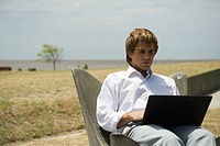 Man using laptop computer outdoors, open field in background