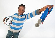 A portrait of a young soccer holding medals and a soccer ball against a white background, Johannesburg, Gauteng Province, South Africa