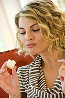 young woman eats a chocolate marshmallow