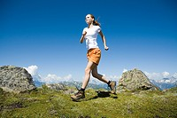 Young pretty woman trekking and running in the mountains