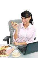 Businesswoman eating pizza in the office