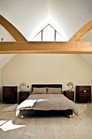 Attic bedroom with wooden beam and wooden floor
