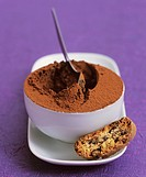 A bowl of mocha mousse with a biscuit