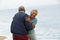 Senior couple embracing by ocean