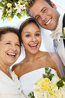 Bride and Groom with mother outdoors close_up portrait