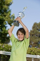 Boy on tennis court Holding up Tennis Trophy portrait