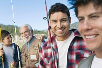 Male members of three generation family on fishing trip focus on mid adult man portrait