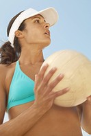 Beach volleyball player holding volleyball preparing to serve