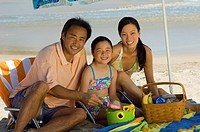Parents with daughter 7_9 having picnic on beach portrait