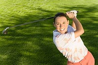 Female golfer swinging golf club elevated view portrait