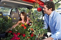 Couple loading plants into car