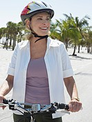 Senior woman on bicycle on tropical beach