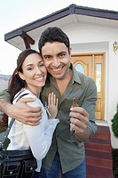 New homeowners standing in front of house holding key portrait