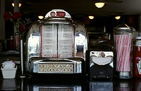 Juke box, paper napkins in dispenser and straws